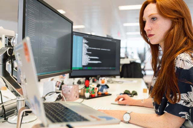 Cybersecurity professional woman at desk with open laptop and large monitor